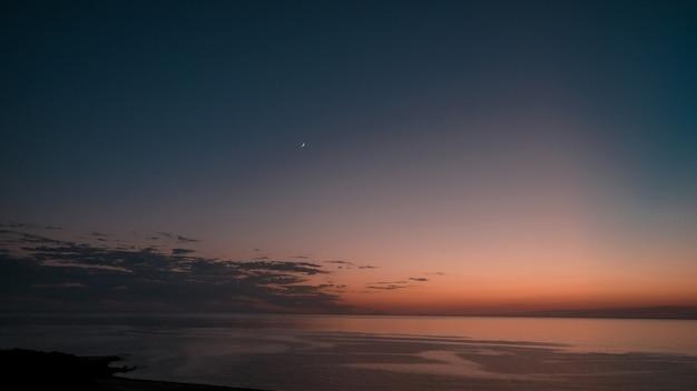 Increíble foto de un hermoso paisaje marino en una puesta de sol naranja