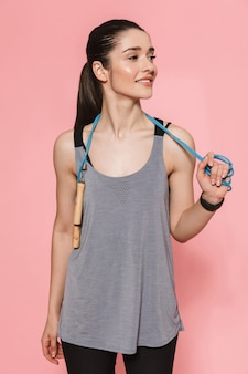 Increíble hermosa joven bastante fitness mujer hacer ejercicios deportivos con saltar la cuerda aislado sobre la pared rosa