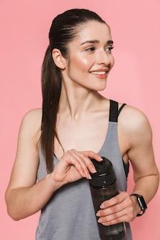 Increíble hermosa joven bastante fitness mujer sosteniendo una botella con agua potable aislado sobre la pared rosa
