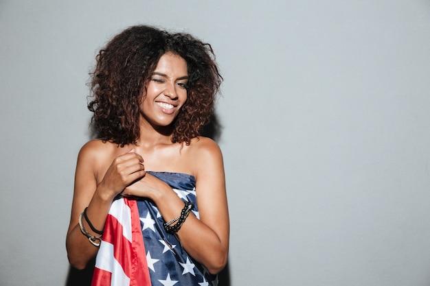 Increíble joven africana de pie vestida con la bandera de estados unidos