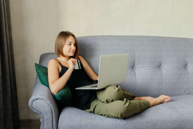 Increíble joven alegre con una tarjeta de débito al hacer una compra de reserva en línea a través de la computadora portátil. concepto de compra en línea, en casa