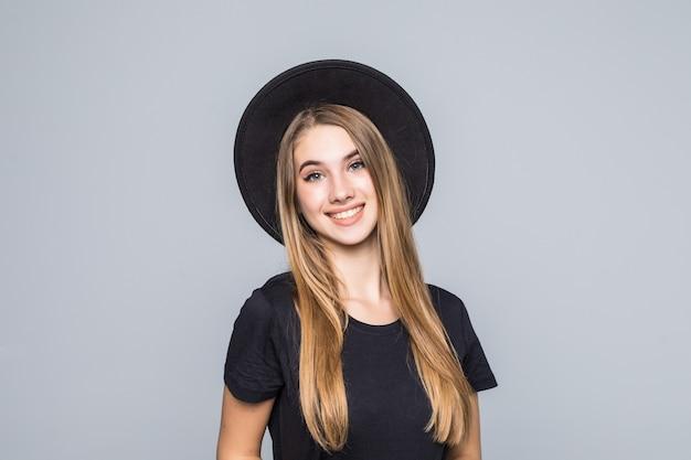 Increíble joven con cabello dorado vestida de negro con sombrero retro sonríe aislado sobre fondo