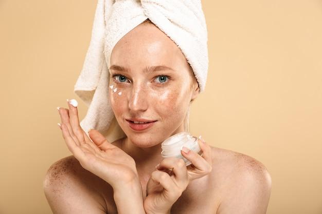 Increíble joven pelirroja cuida su piel con crema.