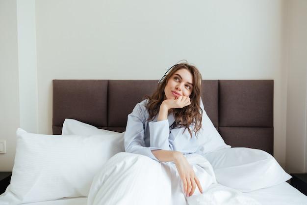 Increíble jovencita vestida con pijama yace en la cama