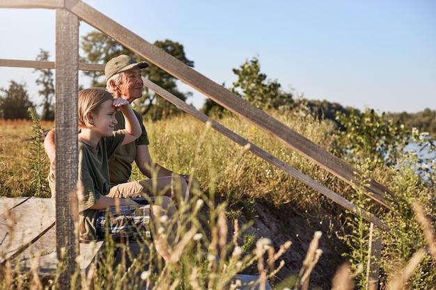 Increíble lugar para pescar, dos hombres preparándose para pescar en el lago, padre e hijo sentados en un lugar de madera cerca del río, un niño rubio mirando lejos con la mano cerca de la frente.