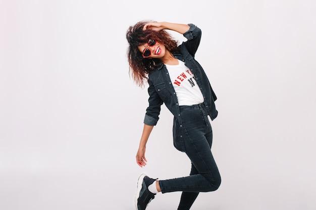 Increíble modelo de mujer delgada en pantalones negros de pie sobre una pierna aislada con sonrisa. chica morena rizada bailando en zapatillas de moda y sonriendo.