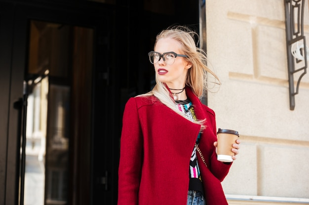Increíble mujer caucásica joven caminando al aire libre tomando café.