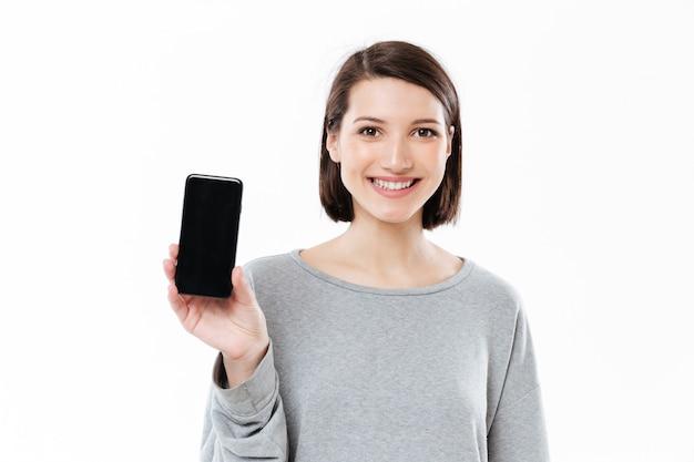 Increíble mujer caucásica joven mostrando la pantalla del teléfono.