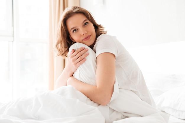 Increíble mujer joven en la cama en el interior con almohada