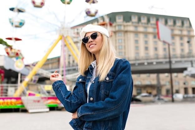 Increíble mujer joven feliz con una sonrisa encantadora vestida con chaqueta vaquera y blusa blanca, gafas de sol negras posando en la ciudad junto a un parque de atracciones