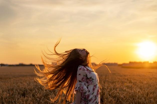 Increíble mujer joven con pelo largo y rizado. mujer en vestido posando en el campo de trigo al atardecer y alisa el cabello inclinando la cabeza hacia atrás
