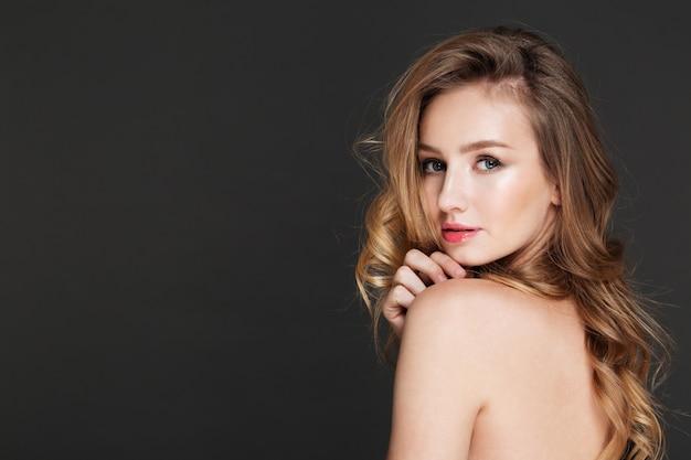 Increíble mujer joven posando sobre pared gris