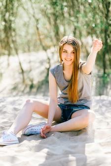 Increíble mujer joven sentada en la arena y divertirse en un día soleado.