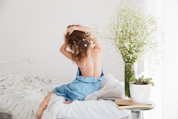 Increíble mujer joven sentada en el interior de la cama estirando.