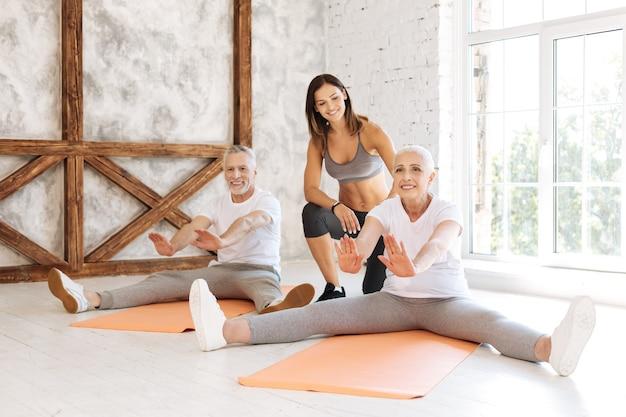 Increíble mujer manteniendo una sonrisa en su rostro y sentada en la alfombra mientras hace ejercicios deportivos