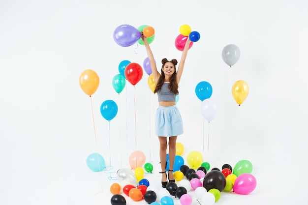 Increíble mujer mirando directamente, sosteniendo globos de helio en blanco