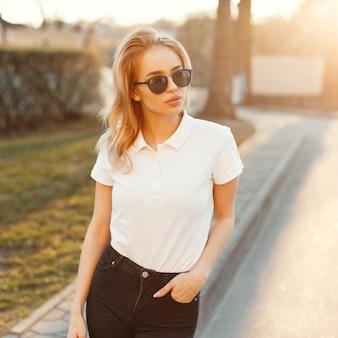 Increíble mujer de moda joven hipster en ropa de verano con estilo está de pie y posando al atardecer de verano. muchacha atractiva. ropa de estilo americano.