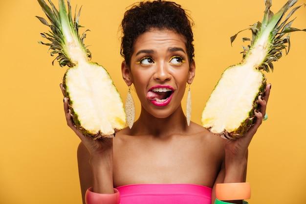 Increíble mujer mulata con maquillaje colorido mirando hacia arriba y lamiéndose los labios mientras sostiene dos partes de piña madura apetitosa aislada, sobre amarillo
