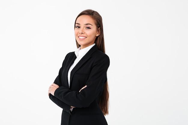 Increíble mujer de negocios alegre de pie con los brazos cruzados