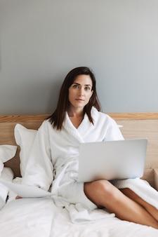 Increíble mujer de negocios joven y bella en el interior de su casa usando la computadora portátil.
