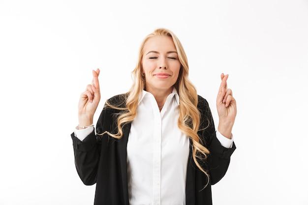 Increíble mujer de negocios posando aislada sobre pared blanca hace gesto de esperanza.