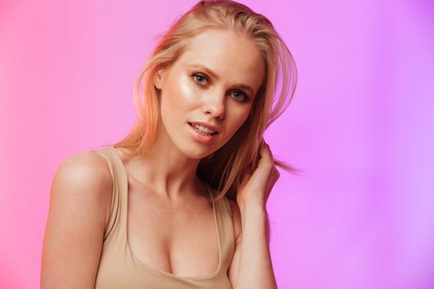 Increíble mujer de pie y posando sobre pared rosa