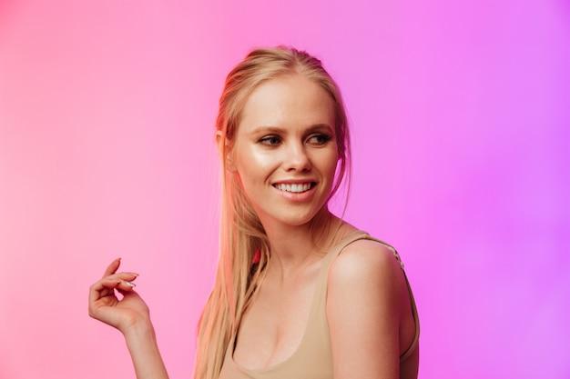 Increíble mujer de pie y posando sobre pared rosa.