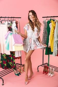 Increíble mujer de pie en la tienda cerca del perchero y sosteniendo coloridas bolsas de compras aisladas en rosa