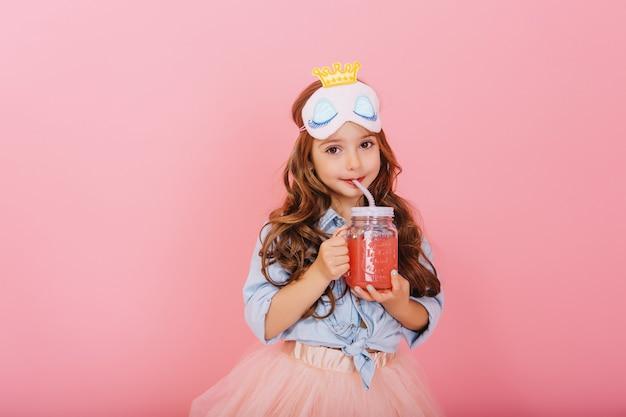 Increíble niña linda con máscara de princesa en la cabeza, cabello largo morena bebiendo jugo de vidrio y mirando a cámara aislada sobre fondo rosa. poca felicidad, expresando verdaderas emociones positivas.