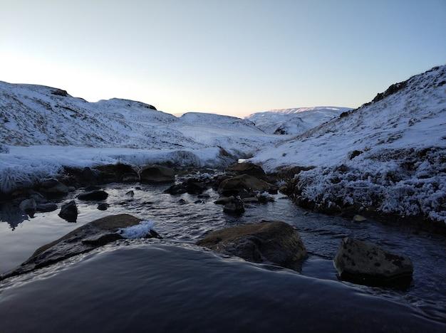 Increíble paisaje invernal de islandia. en invierno, una fuente de agua caliente fluye en las montañas.