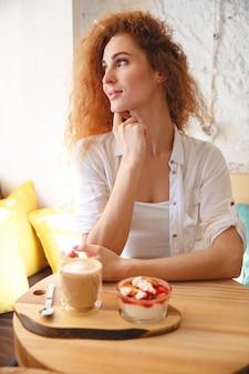 Increíble pelirroja jovencita sentada en la cafetería mientras se come el postre.