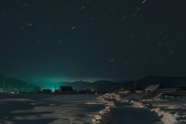 Increíble pueblo nevado con hermosas casas y puente sobre un pequeño río bajo el claro cielo estrellado nocturno