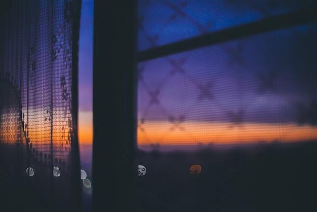 Increíble puesta de sol romántica en la ventana detrás de siluetas de textura de tul. maravilloso cielo naranja violeta azul amanecer desde la ventana a través de la cortina.