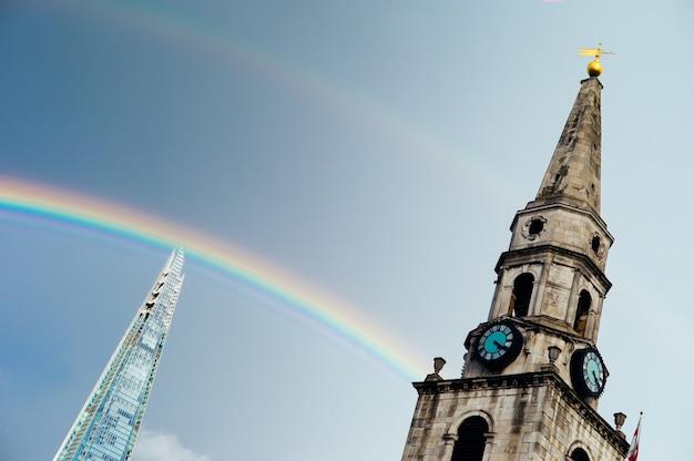 Increíble torre del reloj y un rascacielos en un hermoso arco iris