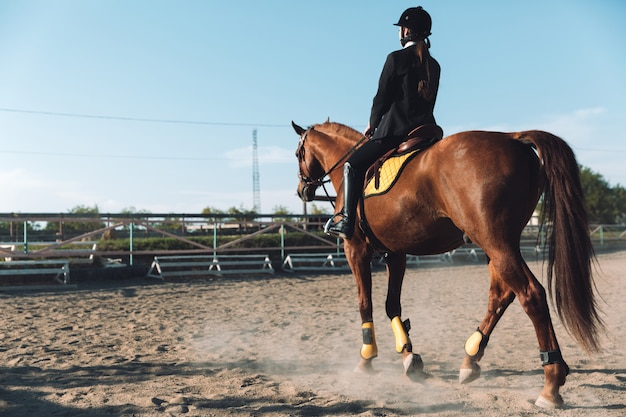 Increíble vaquera joven sentada a caballo al aire libre