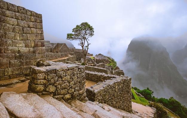 Increíble vista del majestuoso paisaje del templo de machupicchu cubierto de niebla en el fondo