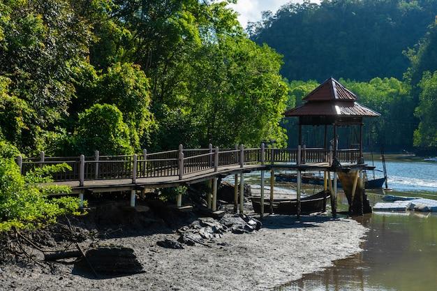 Increíblemente hermoso paisaje natural, un muelle para botes al río, en un bosque verde con vista a las montañas.