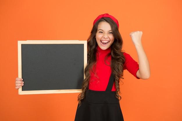 Increíbles noticias. programa educativo. información del horario escolar. estudiante francés lindo de la muchacha de la escuela mantenga el espacio de la copia de la pizarra. concepto de anuncio escolar. cambios en la vida escolar. gesto de éxito.