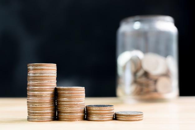 Incremento de aumento de la pila de monedas ahorre dinero con fondo de tarjas borrosa