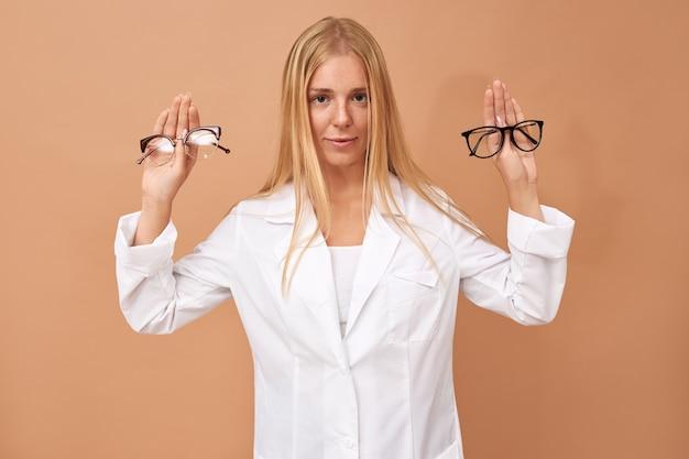 Indeciso hermosa joven clienta sosteniendo gafas con expresión facial dudosa
