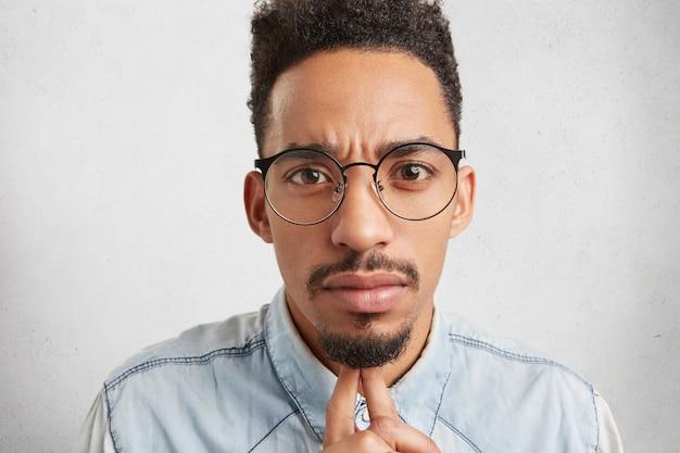Independiente hombre seguro usa gafas redondas, mira seriamente