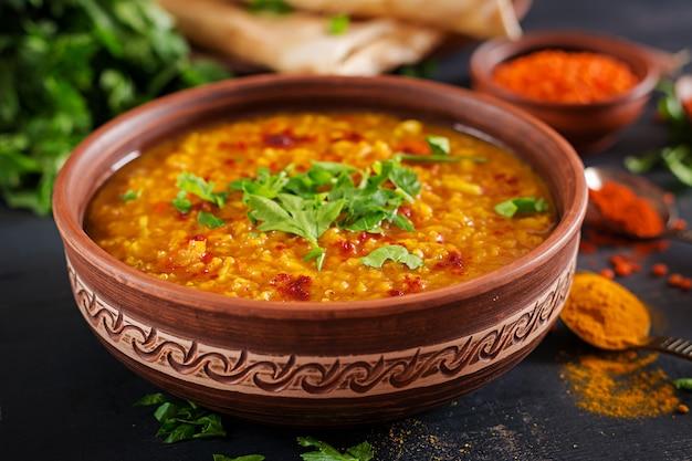Indian dhal curry picante en un tazón, especias, hierbas, fondo rústico de madera negra.