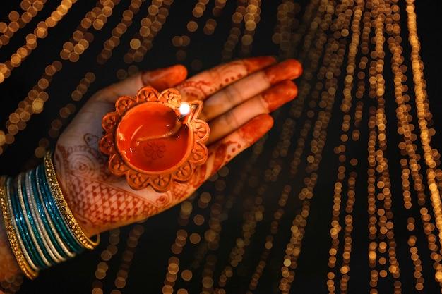 Indian festival diwali, lámpara de aceite decorativa en mano