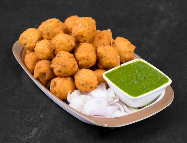 Indian spicy street food dal vada sobre fondo negro
