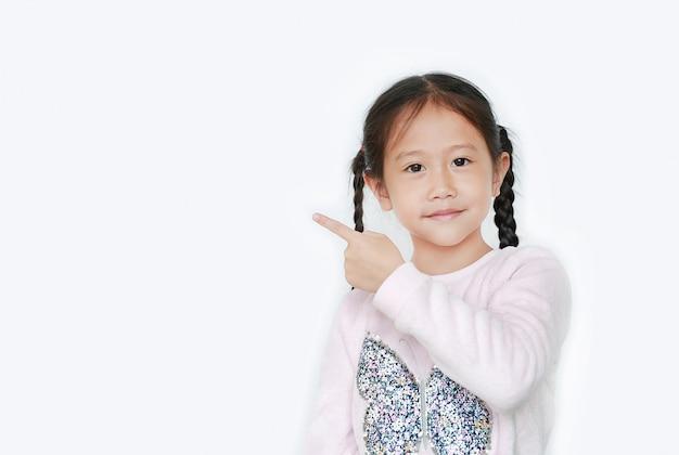 El índice alegre del punto de la muchacha del niño pequeño al lado para presentar algo aislado con el espacio de la copia. colegiala asiática en concepto de educación.