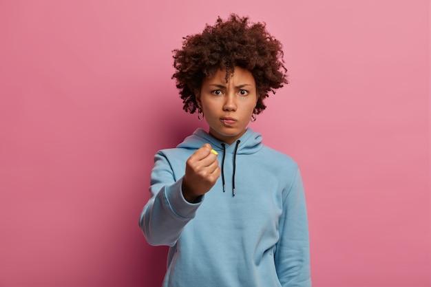 Indignada mujer afroamericana aprieta el puño y mira enojada