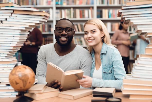 Individuo africano y muchacha blanca rodeados por los libros en biblioteca.