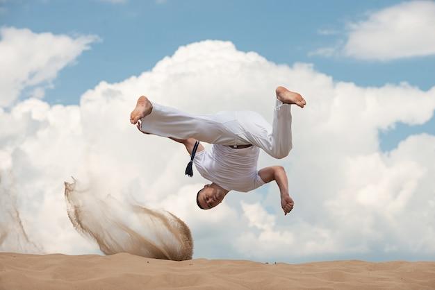 El individuo joven entrena a capoeira en backround del cielo. un hombre realiza la patada marcial en el salto.