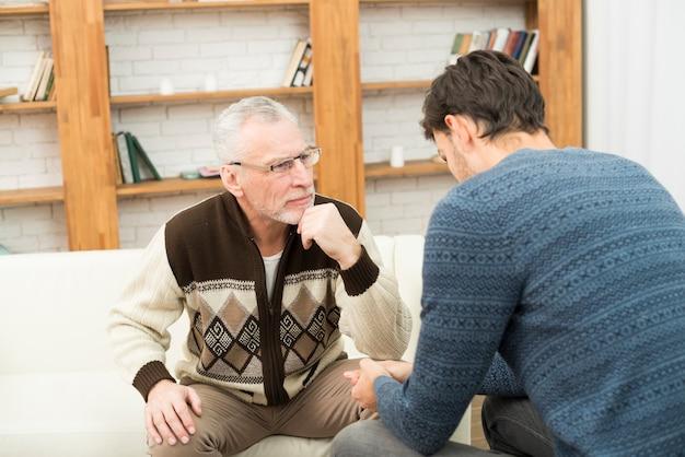 Individuo joven y hombre concentrado envejecido en el sofá en sitio