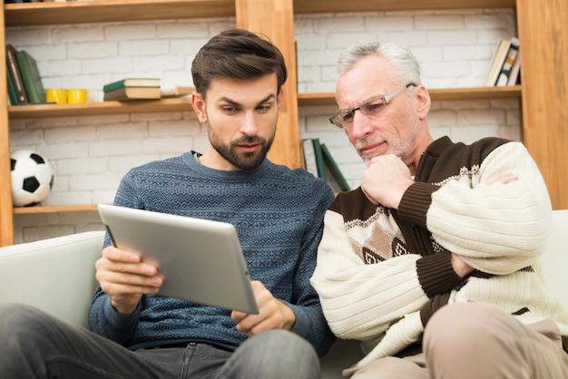 Individuo joven y hombre envejecido que usa la tableta en el settee